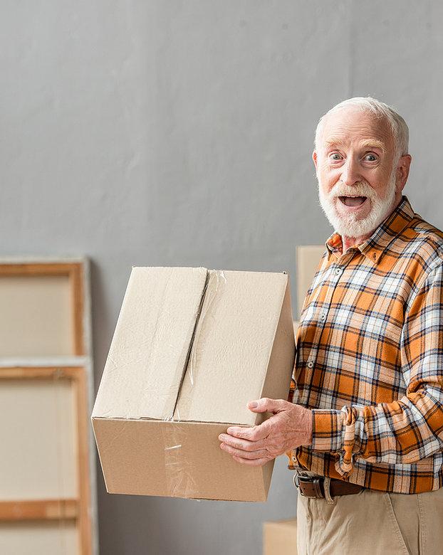 Älterer Herr hält einen Karton in den Händen